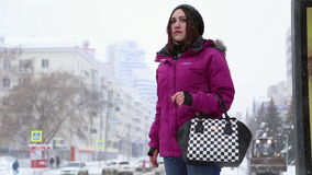 A girl stands at the bus stop in winter stock footage