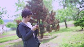 Girl dreams and writes a message on the smartphone. Girl stands in a city park, dreams and writes a message on a smartphone stock video footage