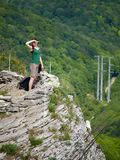 A girl stands on a cliff against the background of green forest royalty free stock image
