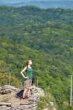 A girl stands on a cliff against the background of green forest stock photos