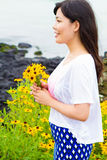 Girl stands in daisy sunflower field near the beach Stock Image