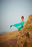 A girl stands on the edge of a cliff. Stock Image