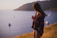 A girl stands on the edge of the cliff near the sea or ocean and looking at the sun valley. Woman enjoying a sunset or Royalty Free Stock Photo