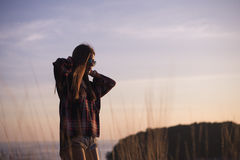 A girl stands on the edge of the cliff near the sea or ocean and looking at the sun valley. Woman enjoying a sunset or Royalty Free Stock Images