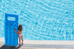 A girl stands on the edge of the pool Stock Photos