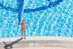 A girl stands on the edge of the pool Stock Photography