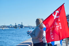 Girl stands on embankment in St. Petersburg and holds Russian flag victory Royalty Free Stock Photography