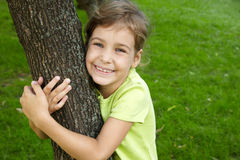 Girl, that stands, embracing tree in park Stock Image