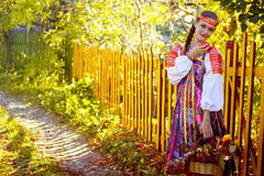 A girl stands by a fence in a Russian costume Stock Photography