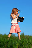 Girl stands in field with clapperboard in hands Royalty Free Stock Images