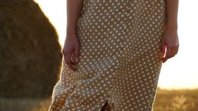 The girl stands in the field after harvest against a sheaf. Gold background. A light breeze moves dress girl in slow. Motion. Close up stock video