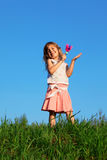 Girl stands in field and knocks rattle in hand Royalty Free Stock Photos