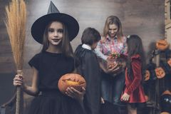 The girl stands in front of her family in a witch`s suit with a broom in her hand and a pumpkin-lighter. A girl in a witch costume and a pumpkin in her hands Stock Images
