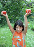 Girl stands in a garden and keeps ripe tomatoes. Over his head Stock Photo