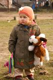 Girl stands on grass. Small girl holds plush dog in hat stock photo