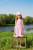 Girl stands on bank of pond, picture frame is at her feet Royalty Free Stock Images