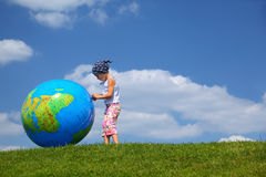 Girl stands on grass and plays with globe. Girl stands on grass in day-time and plays with an inflatable globe Royalty Free Stock Image