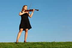Girl stands on grass and plays violin against sky stock photography