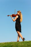 Girl stands on grass and plays violin against sky Stock Images