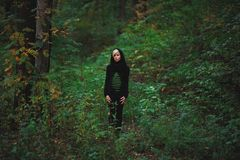 Girl stands among the green forest. And holding fern Royalty Free Stock Image
