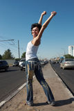 Girl stands in half-turn on middle of road. Girl with lifted hands stands in half-turn on middle of road among cars Royalty Free Stock Image