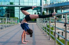 Girl stands on the hands, upside down. Acrobatics Royalty Free Stock Photos