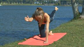 Girl Stands in Hard Yoga Position on Lake Bank Grass. Closeup slim athletic girl stands in hard yoga position on large blue lake bank with fresh grass and trees stock video