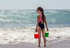The girl stands with her back on the beach against the backdrop of a beautiful wave with pails for playing with sand. Stock Photo