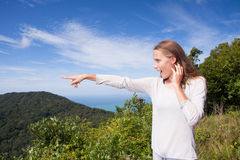 Girl stands on a hilltop points into the distance Stock Photos