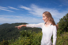 Girl stands on a hilltop points into the distance Royalty Free Stock Photo