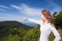 Girl stands on a hilltop points into the distance Stock Images