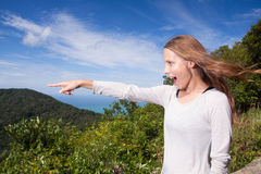 Girl stands on a hilltop points into the distance Stock Photo