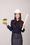 Girl stands with a house builder and drawing in hands Royalty Free Stock Image
