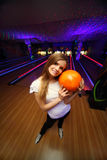 Girl stands and hugs ball in bowling club Stock Photos