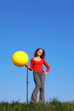 Girl stands and inflates with foot pump balloon Stock Photos