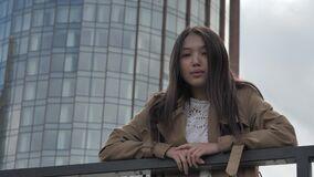 Girl stands leaning against the railing against the backdrop of a tall building