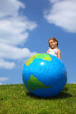 Girl stands and looks aside next to an globe Royalty Free Stock Images