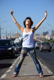 Girl stands on middle of road with rised hands Stock Image