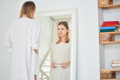 Girl stands at a mirror and is behind the stomach Royalty Free Stock Image