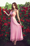 Girl stands on nature on a background of roses Royalty Free Stock Photo