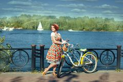 Girl stands near a bike on the riverside Stock Images