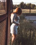 Girl stands near the iron grid in a gray blouse and shorts Royalty Free Stock Photo