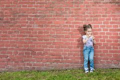 Girl stands near old brick wall. Little girl in jeans with suspenders stands near old brick wall and looking on flower royalty free stock images