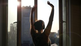 The girl stands near an open window, her hands upwards enjoying the spring warm day and the air in the sun. Lens effect.  stock video footage