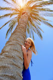 Girl stands near by palm tree Stock Photos