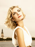 Girl stands near the river. Beautiful blond girl stands near the river Stock Image