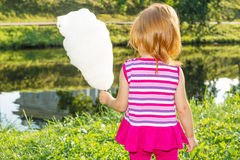Girl stands near the river and keeps the cotton candy Royalty Free Stock Image