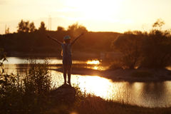 Girl stands near the river at sunset Royalty Free Stock Photos