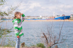 A girl stands near the river on which the floating ship and looks into the distance Royalty Free Stock Photography
