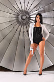Girl stands near silver umbrella in studio Royalty Free Stock Image